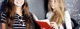 back to school after summer vacations, two teen real girls in classroom with blackboard painted together close up